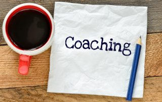 "Mug of coffee, a napkin with the word ""Coaching"" written on it, and a pencil sitting on wooden desk"
